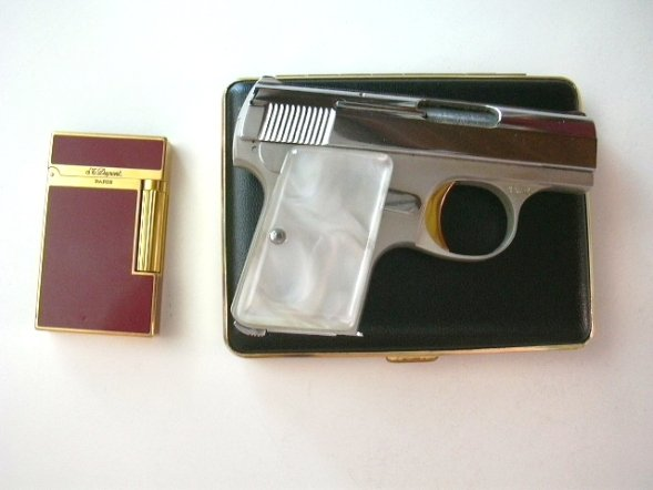 Browning .25 caliber pistol laying on a cigarette case next to st dupont lighter