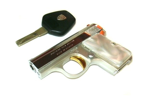 1968 Browning .25 caliber pistol next to a Porsche car key